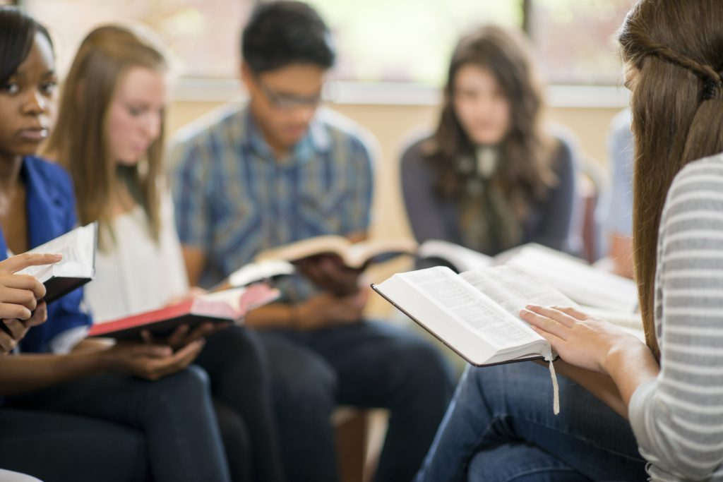 Diverse group of teens studying the Bible.
